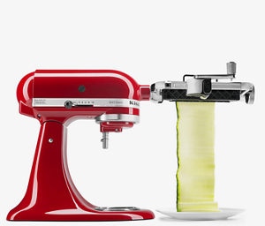 Red stand mixer using fresh prep attachment to cut zucchini into sheets.