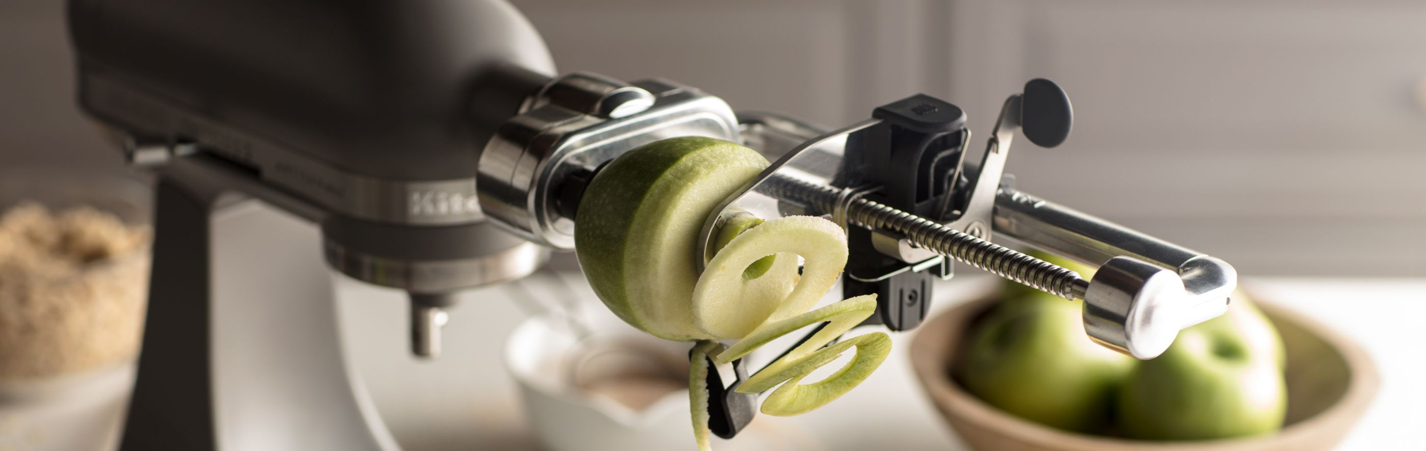 Green, Granny Smith apple being spiralized using a KitchenAid® fresh prep attachment.