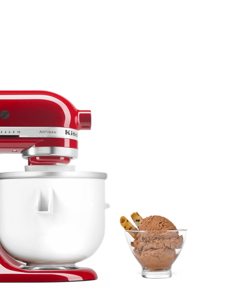 Red stand mixer equipped with ice cream maker next to bowl of chocolate ice cream and wafers.