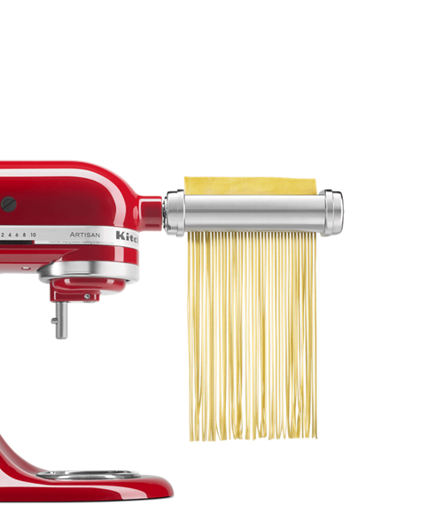Red stand mixer with pasta and grain attachment cutting pasta sheets in linguine shape.