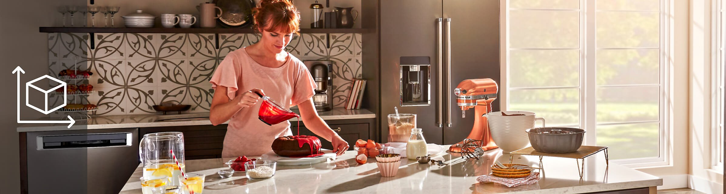 A person drizzling red icing on a cake and baking ingredients and a KitchenAid® stand mixer on the counter