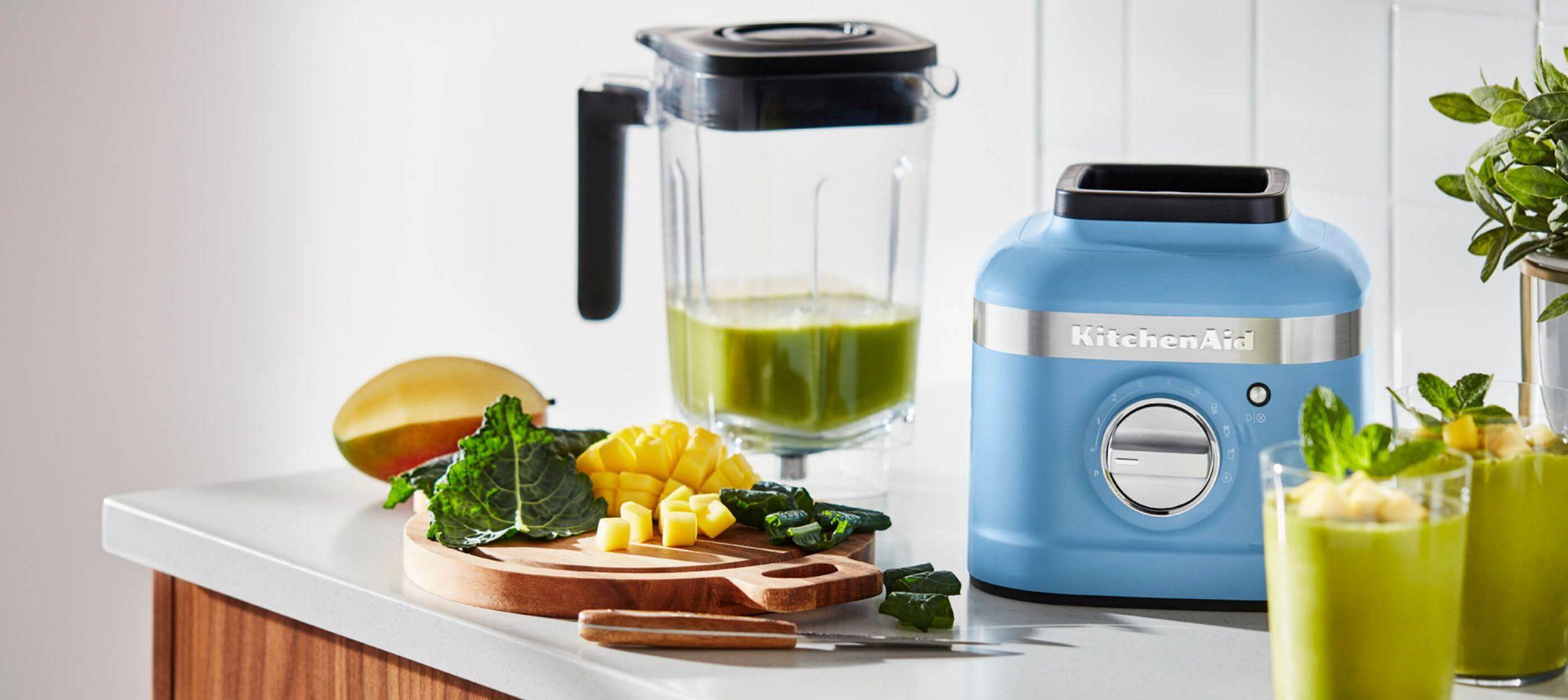 A Blue Velvet K400 Blender holding a green smoothie.