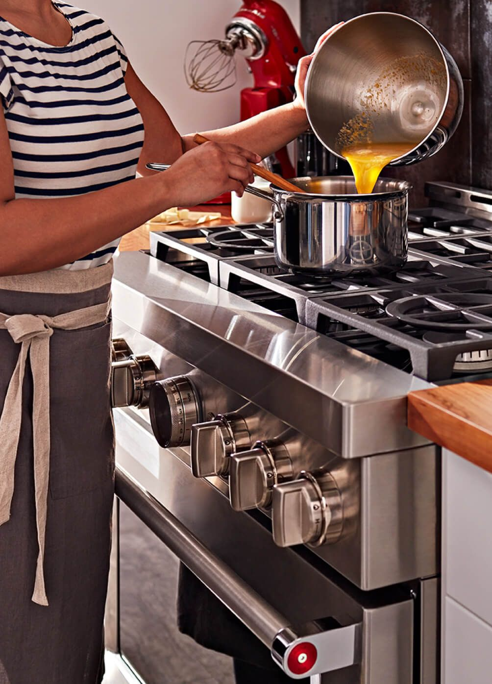 A woman cooks a sauce on a commercial-style range stovetop.