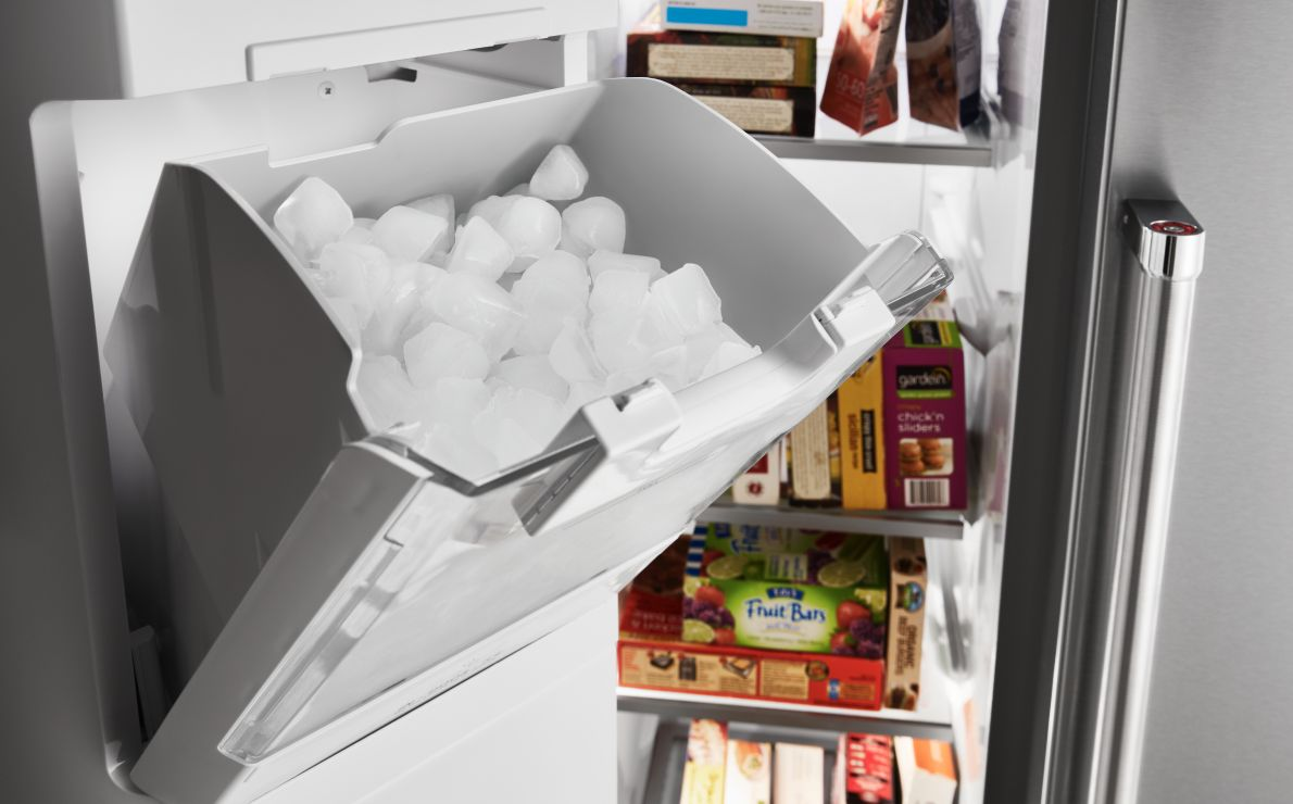 A full ice bin in a KitchenAid refrigerator.