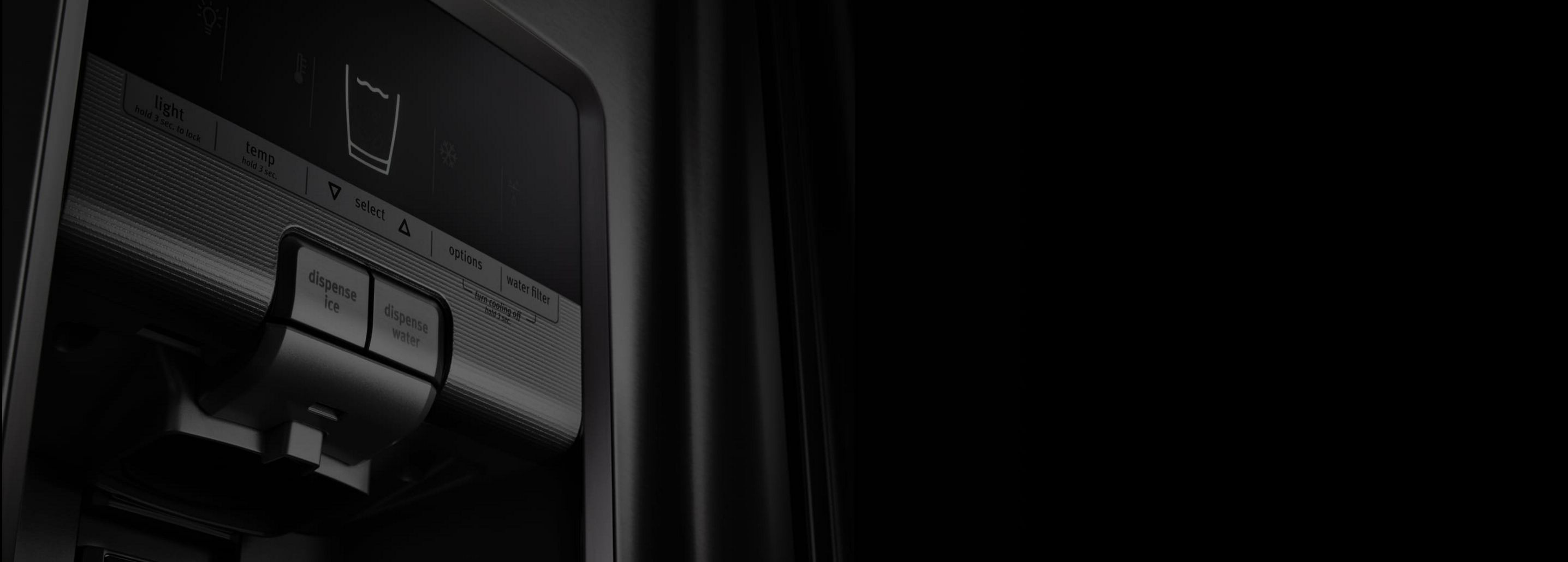Dramatic, close-up shot of a black Maytag refrigerator ice and water dispenser.