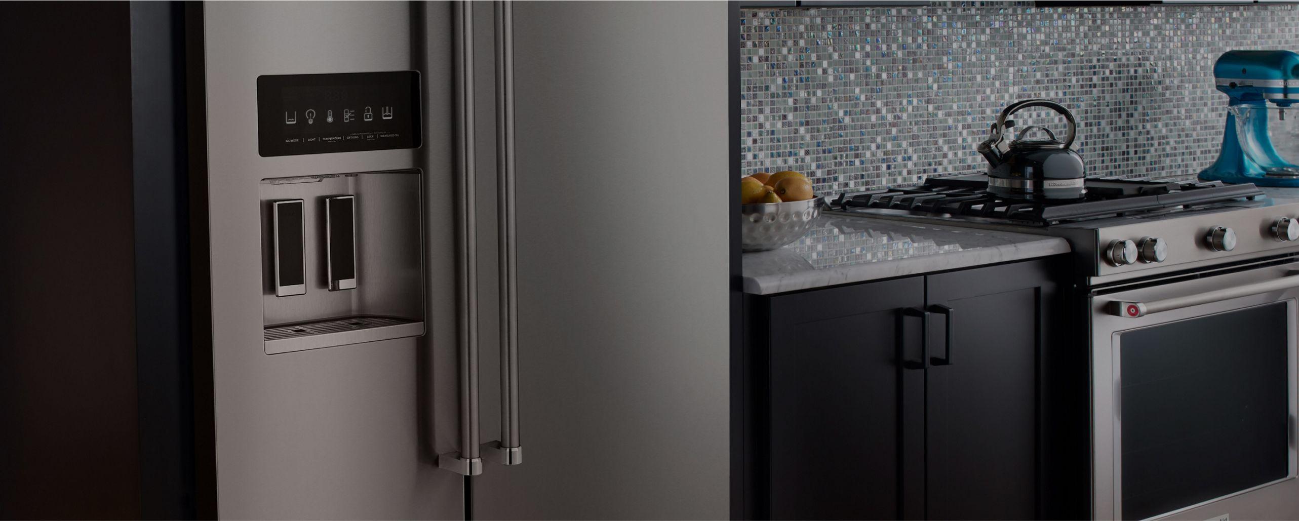 Une image panoramique d'une cuisine avec des appareils KitchenAid, y compris un réfrigérateur en acier inoxydable avec distributeur d'eau
