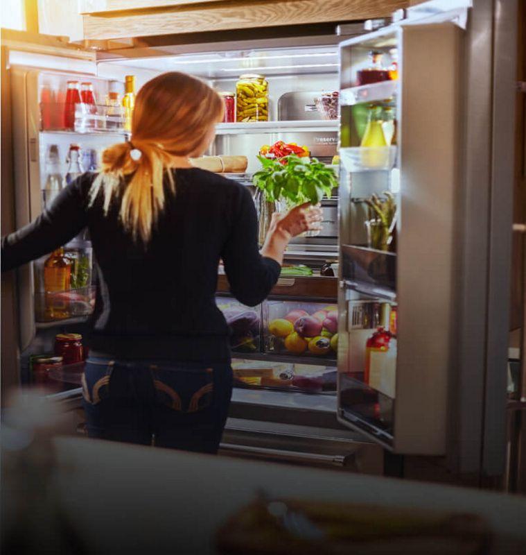 Une personne prenant du basilic frais dans un réfrigérateur