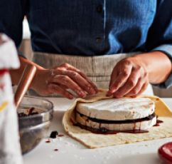 Expert hands gently wrapping homemade crust around a delicate pastry filled with berry preservative.