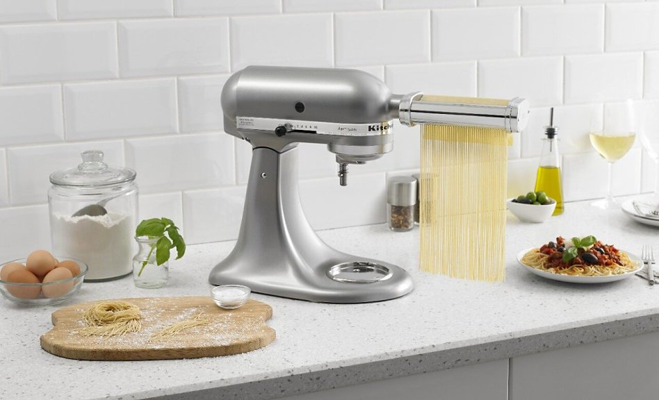 KitchenAid® stand mixer with pasta cutter attachment cutting pasta dough into thin strips.