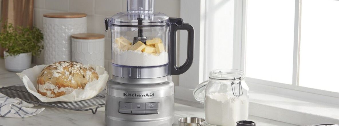 Countertop with KitchenAid® food processor containing flour and butter next to a loaf of bread.