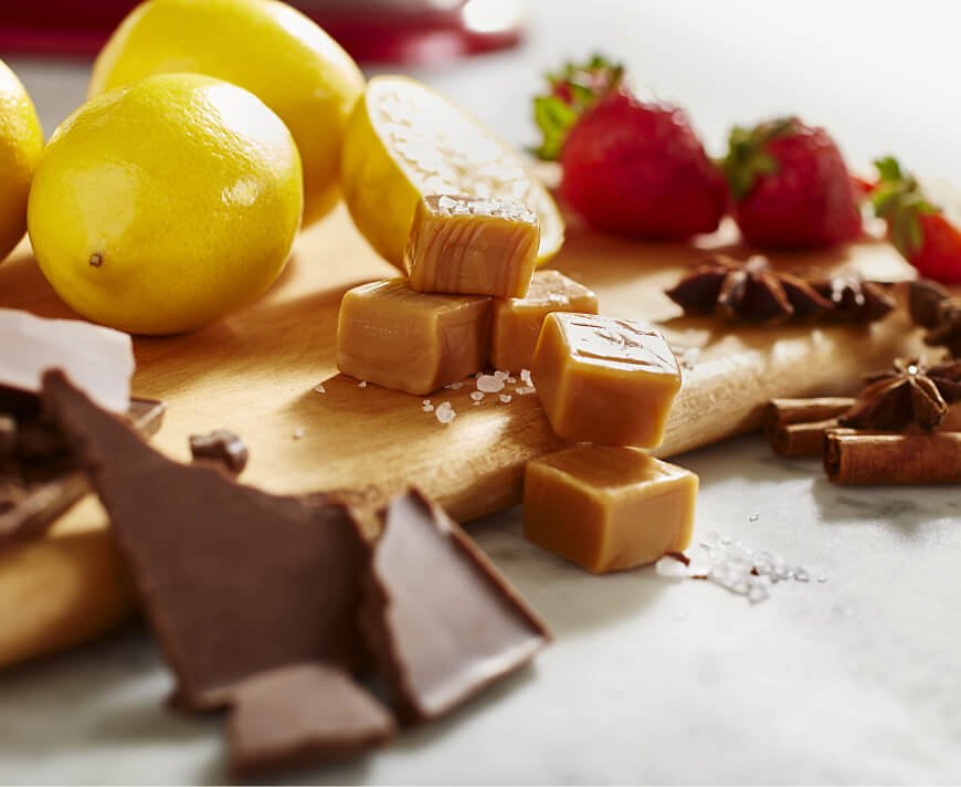 Chocolate, caramel, lemons and strawberries on a wooden cutting board.