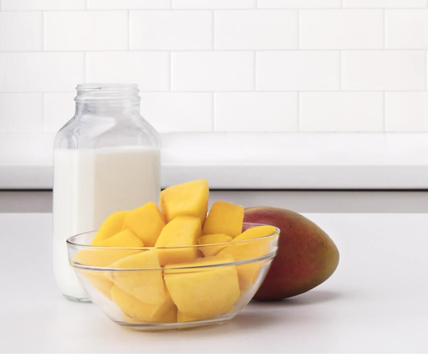 A bowl of sliced mango and a glass of milk.