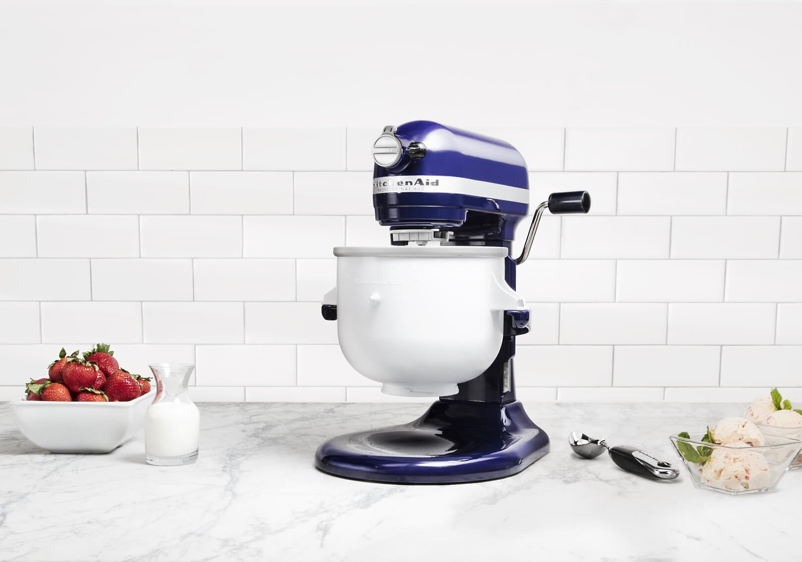 A KitchenAid® bowl-lift stand mixer with strawberries and milk.