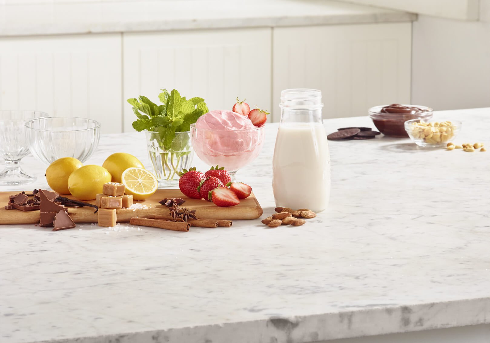 Ingredients and toppings for making frozen yogurt at home.