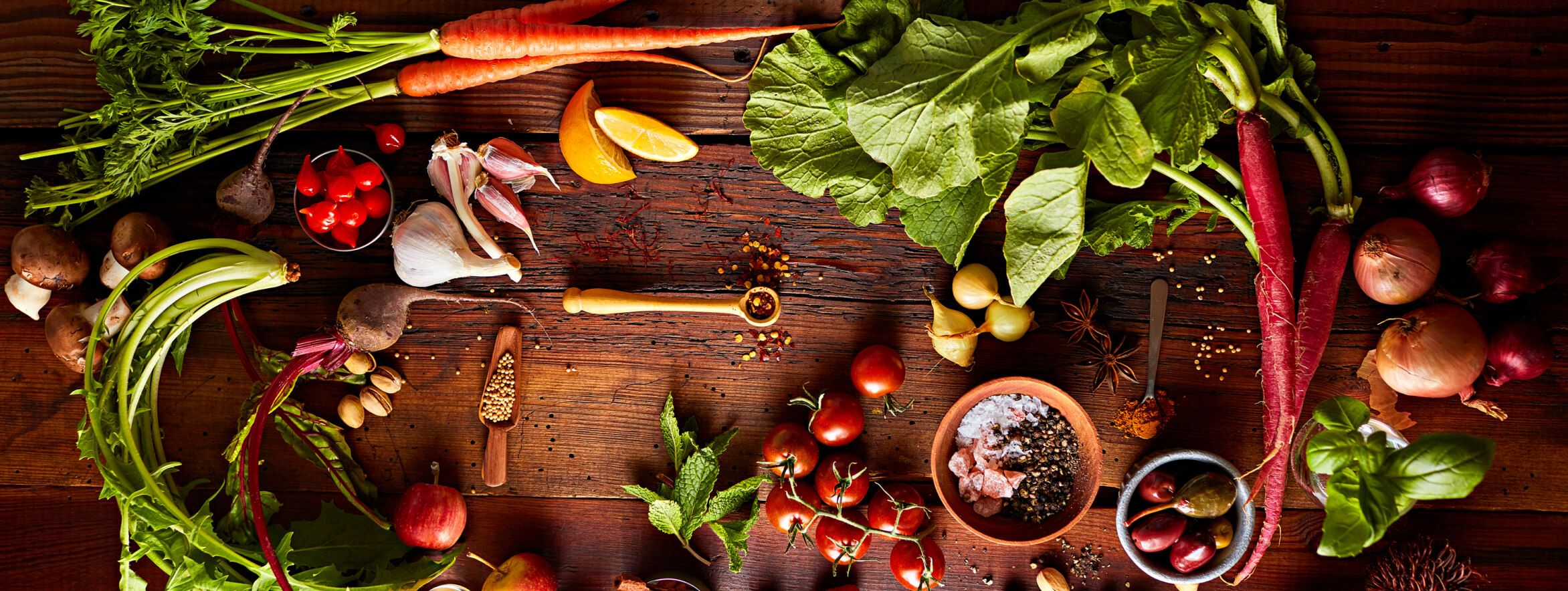 Whole spices, vegetables and fruits arranged on a wood countertop