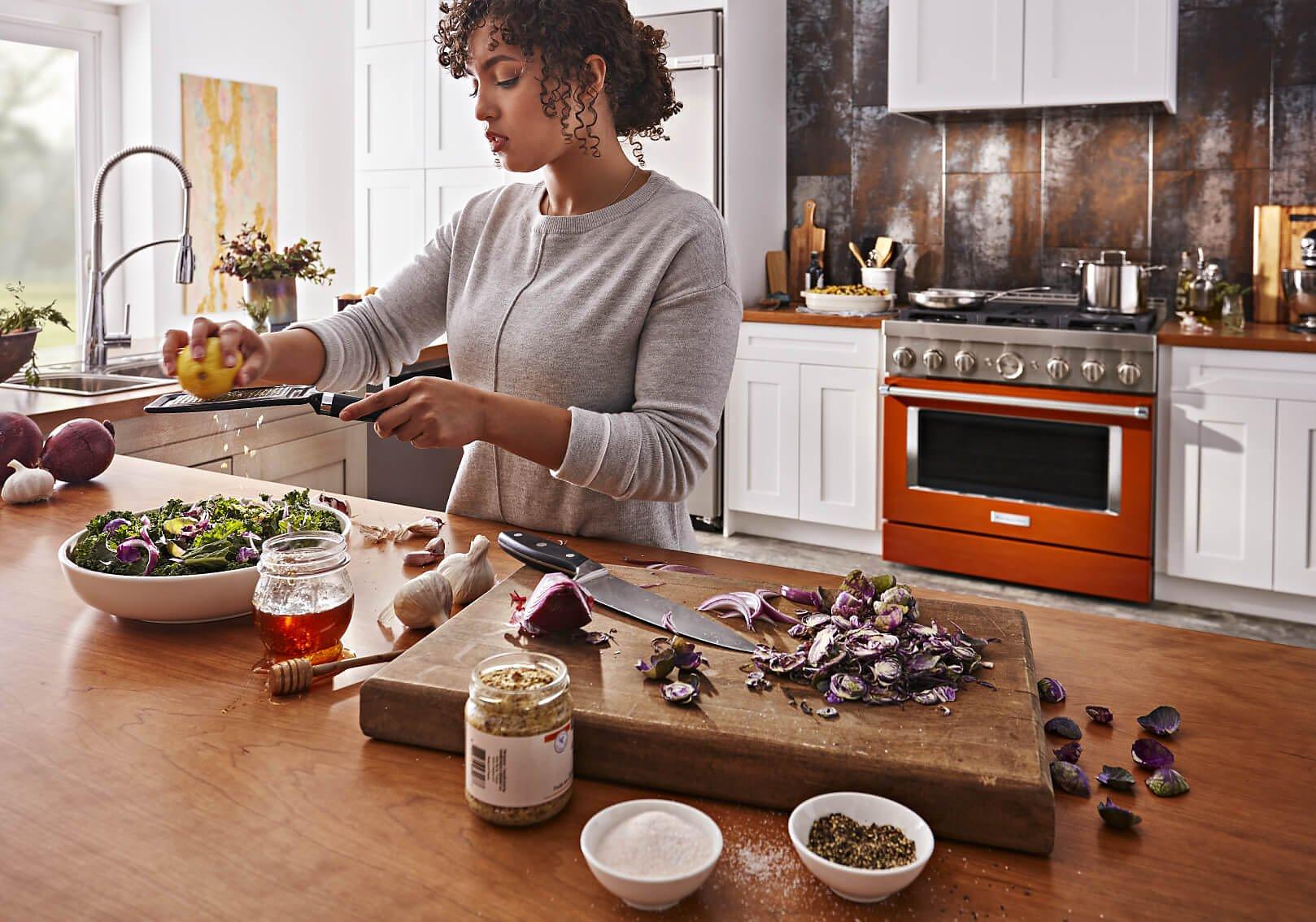 Woman in kitchen preparing a salad