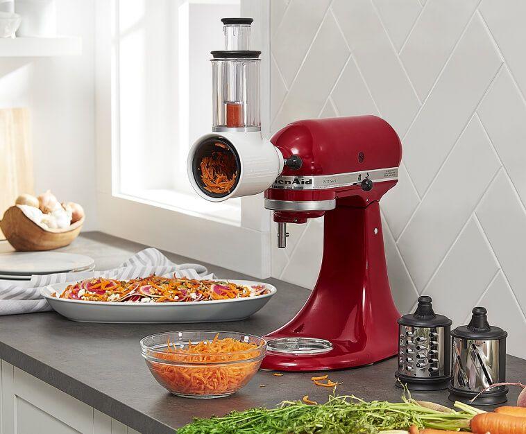 Red KitchenAid® stand mixer with Shredder Attachment shredding carrots