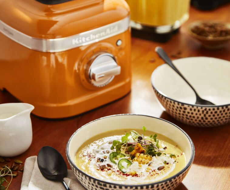KitchenAid® blender in Honey next to a bowl of soup