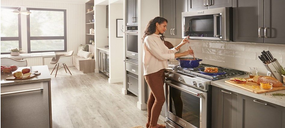Woman pressing a microwave button as she's cooking on the stovetop in an open concept kitchen.