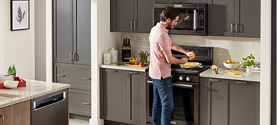 Man cooking on a KitchenAid® range in a kitchen with gray cabinetry.