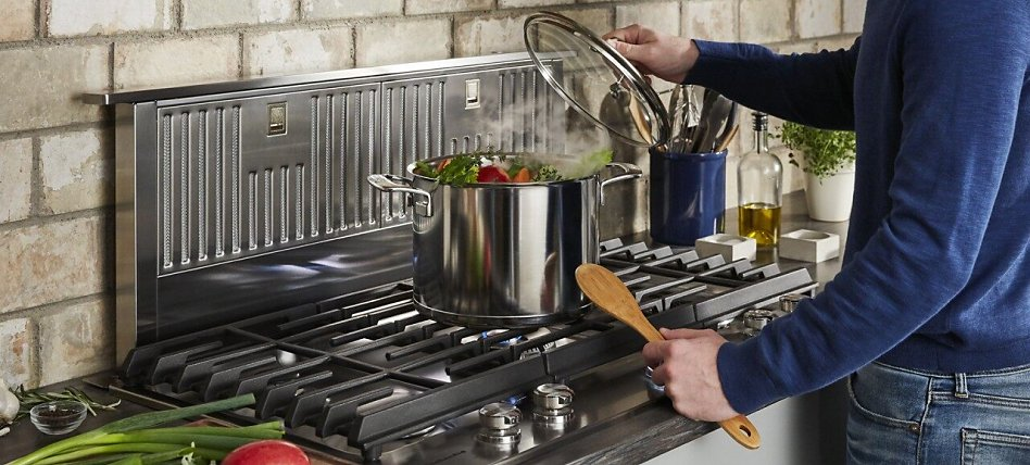 Stock ingredients boiling on a cooktop with a downdraft ventilation system behind it.