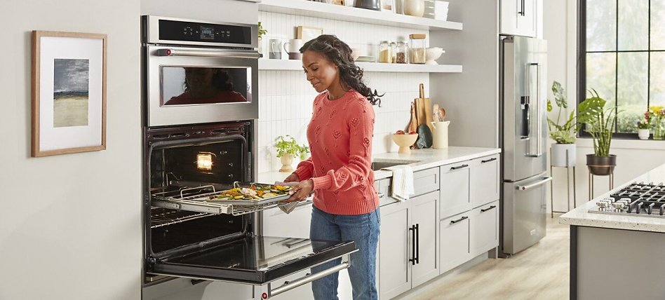 Woman removing a sheet pan from the oven in a bright kitchen with light gray cabinets.