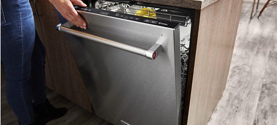 Hand closing a dishwasher in a kitchen island.
