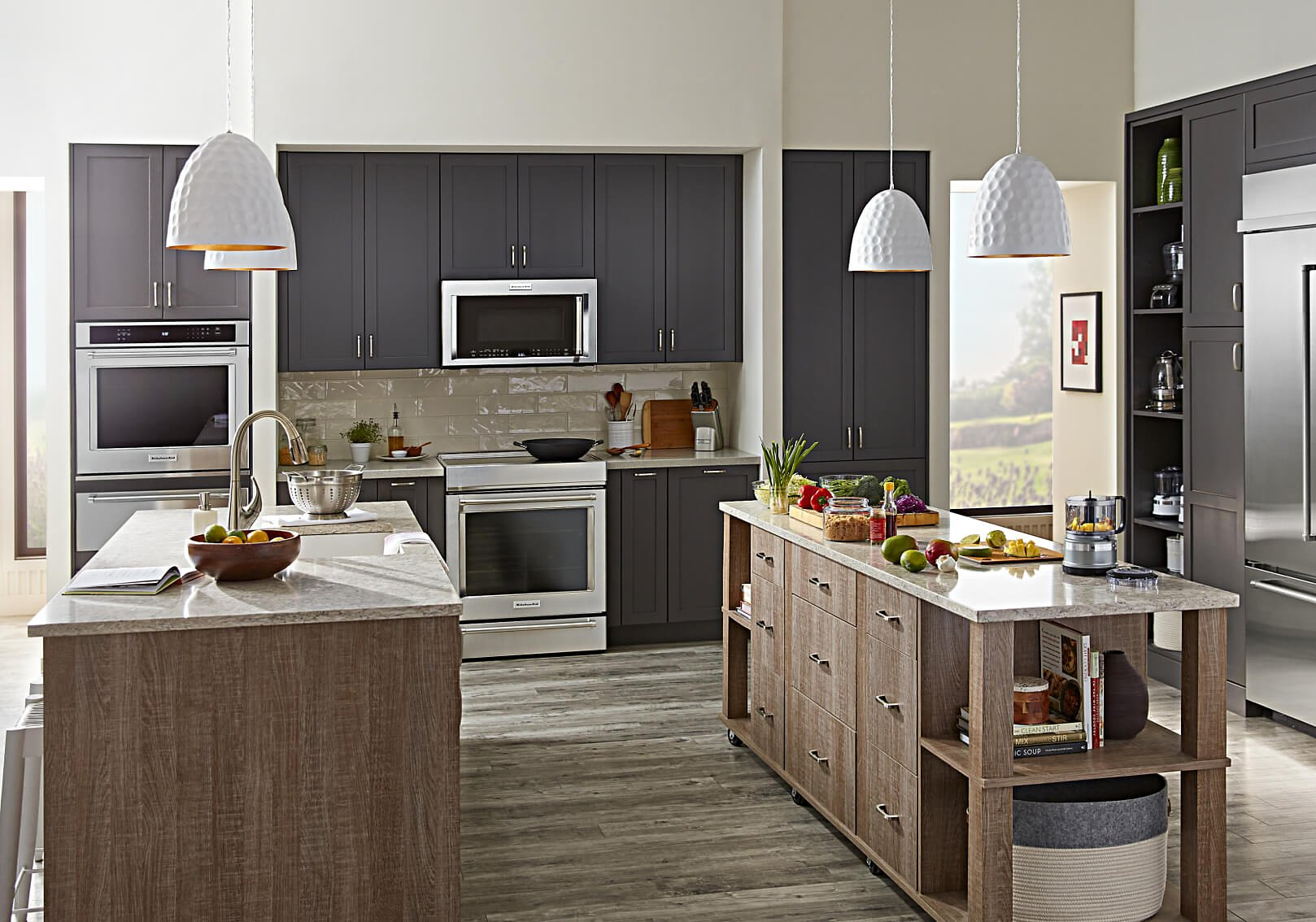 Modern kitchen with grey cabinets, wood paneled island and stainless KitchenAid® appliances.