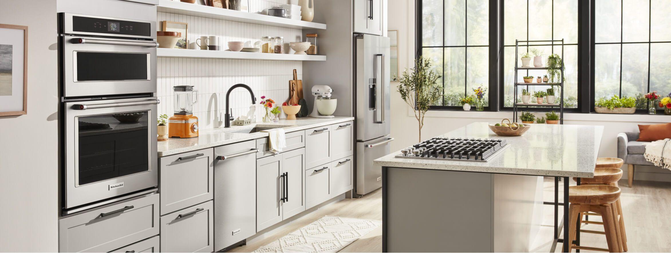 White kitchen with large island and  KitchenAid® appliances.