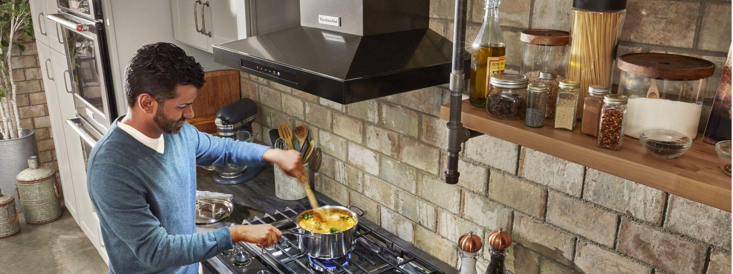 Man stirring a dish on a gas range with hood overhead
