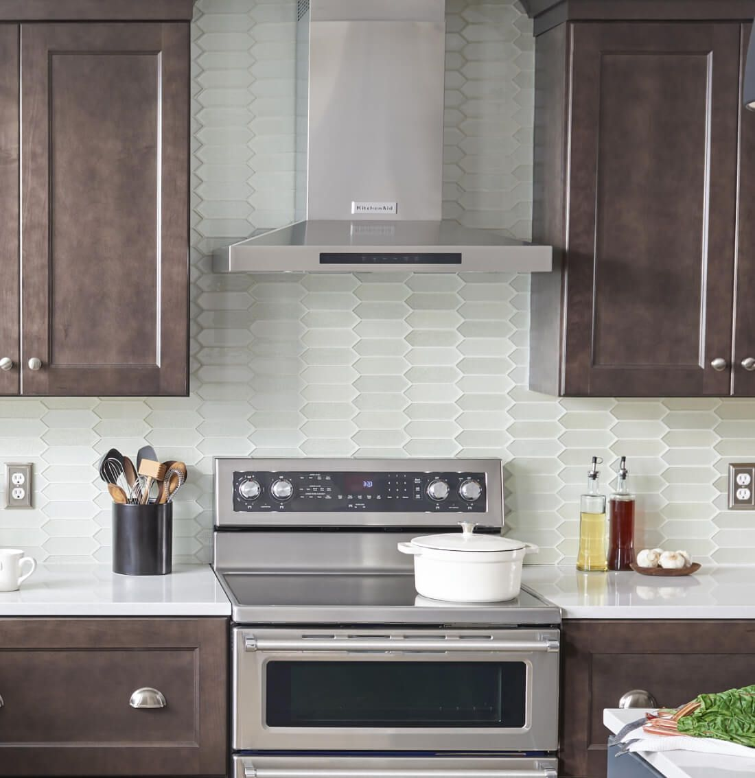 Wall-mount canopy hood between brown cabinets