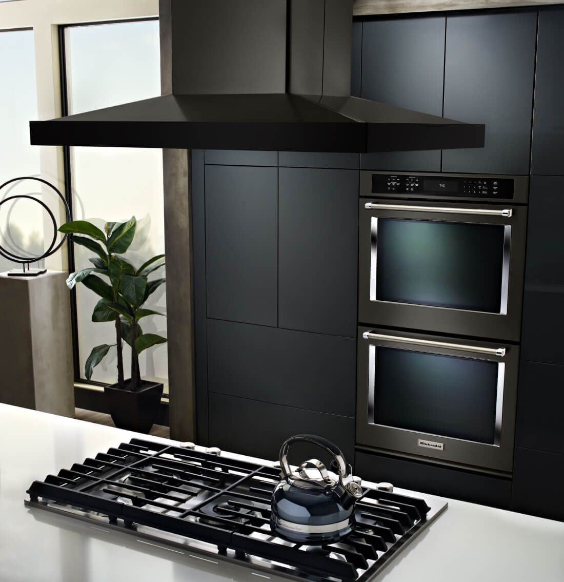 Black island canopy hood over a gas cooktop