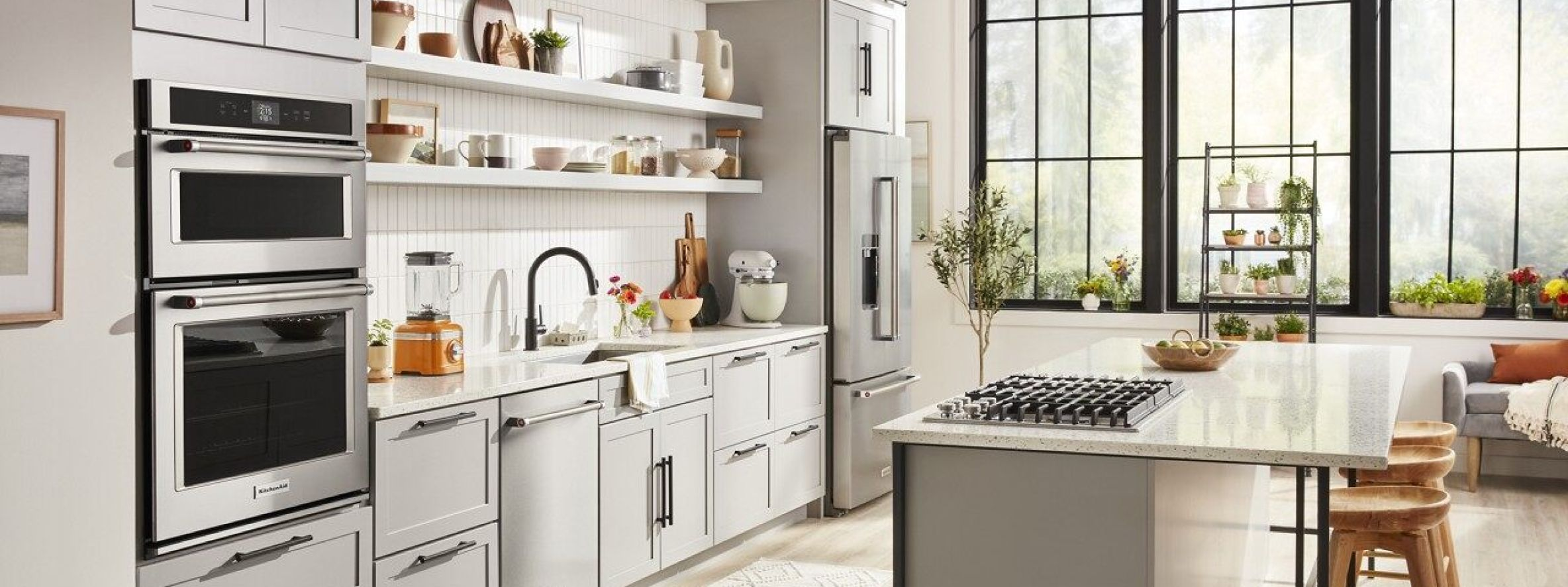 KitchenAid® appliances shown installed in a modern kitchen and bar area.
