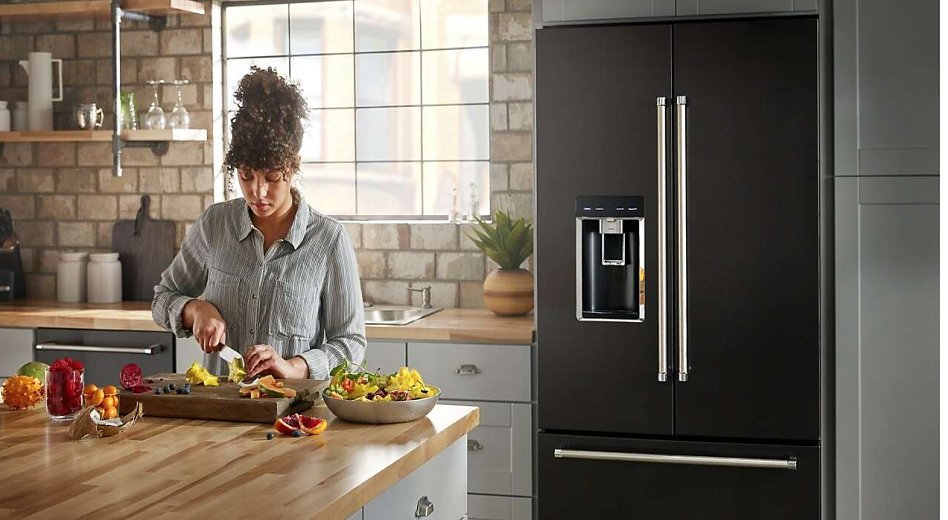 Person preparing food next to a French door refrigerator