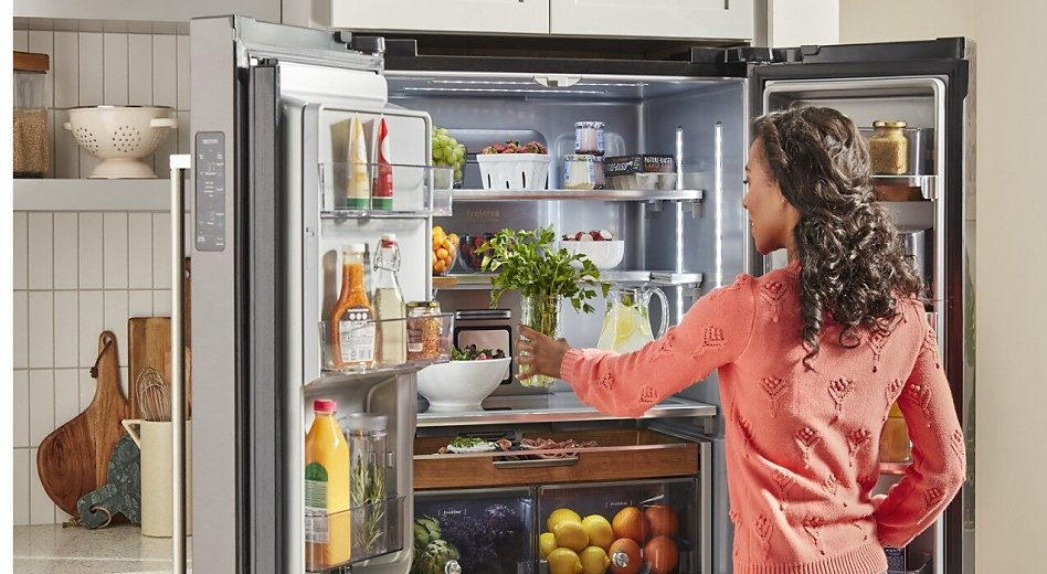 Person putting fresh herbs into a stocked French door refrigerator