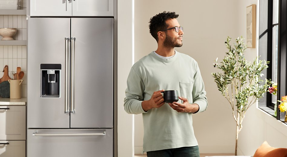 Person holding a mug next to a French door refrigerator