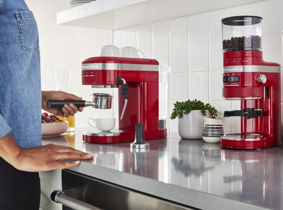 Woman using a red espresso coffee maker and grinder on countertop