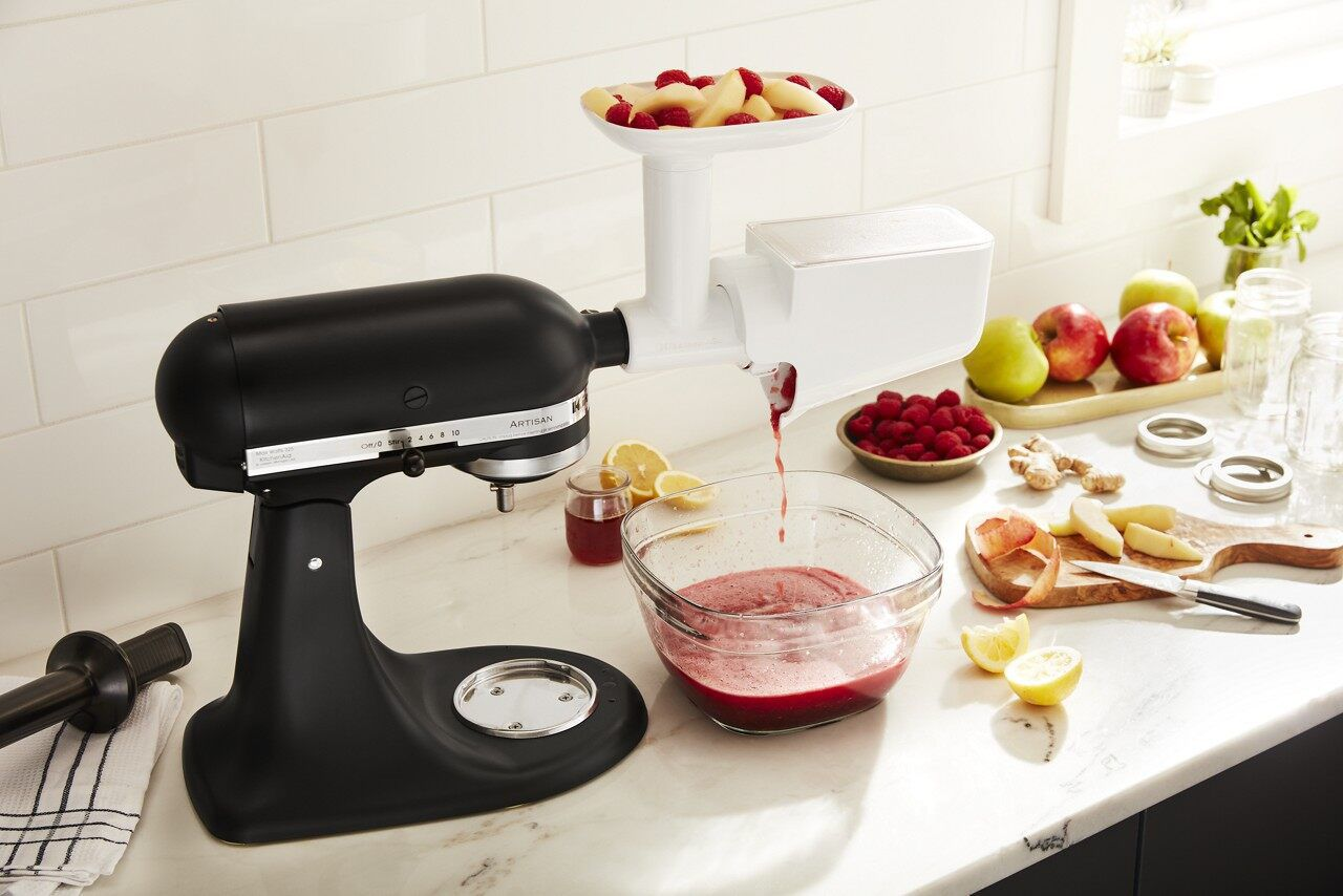 kitchenaid® fruit and vegetable strainer attachment on black stand mixer pureeing fruit
