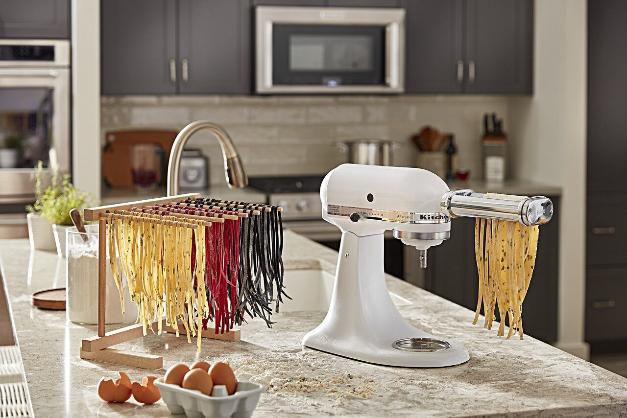 Pasta attachment on white stand mixer cutting noodles