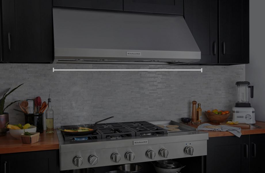 Under-cabinet KitchenAid® hood above a KitchenAid® gas range with food cooking in pan and an animated hood width measurement overlay