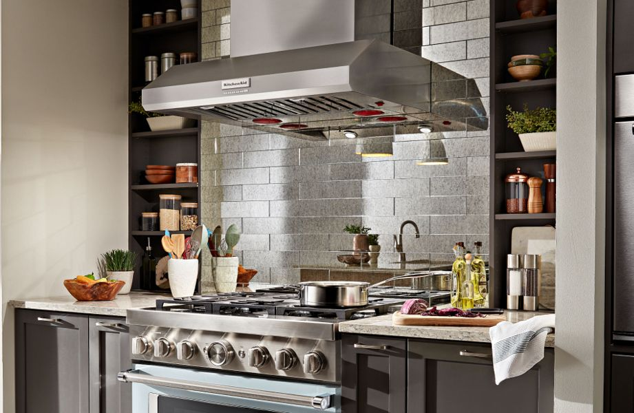 Wall-mount commercial-style KitchenAid® hood above KitchenAid® gas range with animated overlay of height, width and depth markers