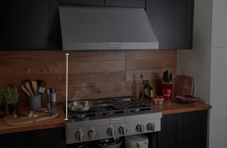 KitchenAid® wall-mount hood above gas range with food cooking in pan, featuring animated height measurement overlay.
