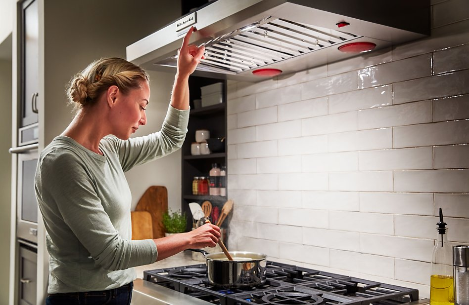 Woman stirring a pot on the cooktop while turning on the under cabinet range hood