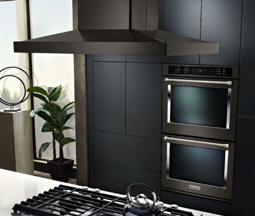 Island mount hood over a cooktop in an island countertop in front of a double wall oven