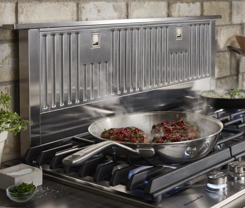 Filets cooking in a pan on a cooktop with a downdraft range hood behind it