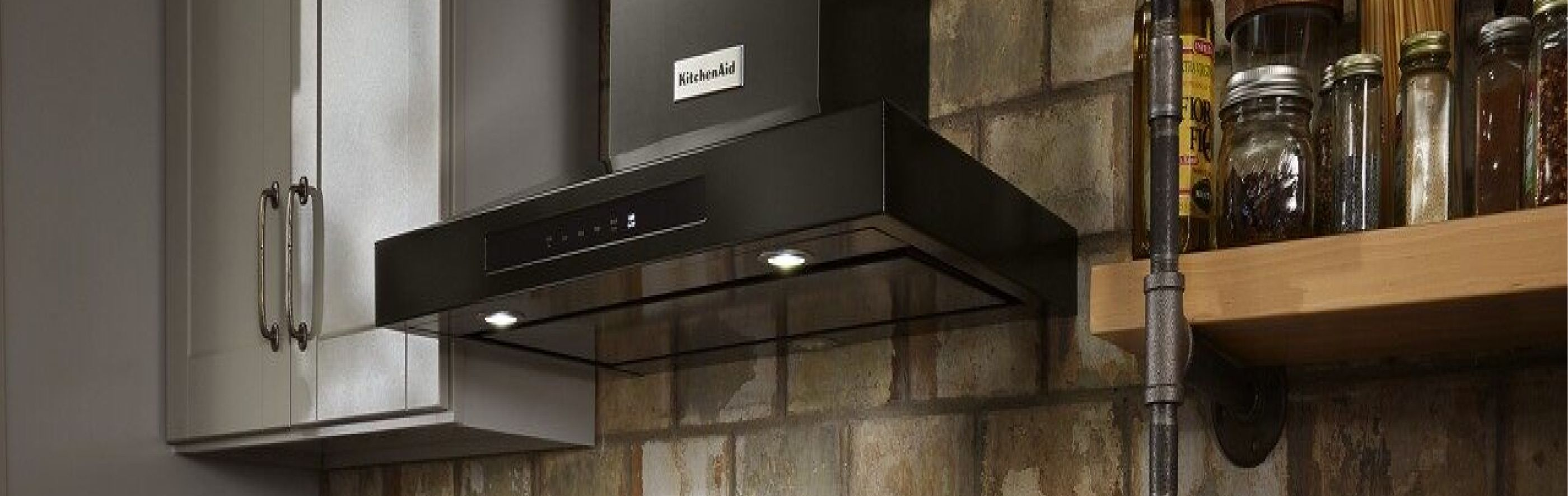 Black KitchenAid® wall mount hood in a kitchen in front of a brick wall