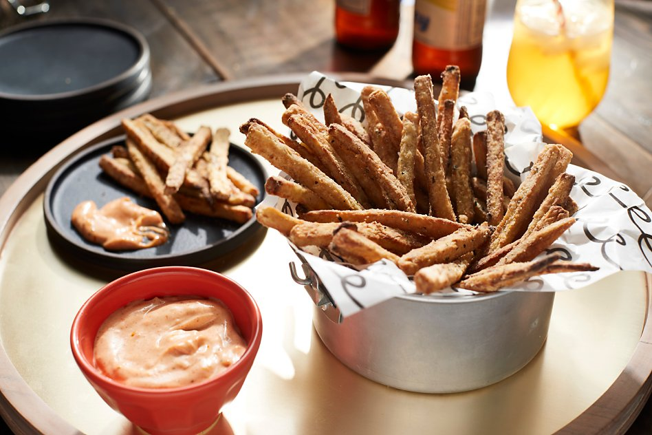 Homemade air-fried french fries and dipping sauce sitting on tray.