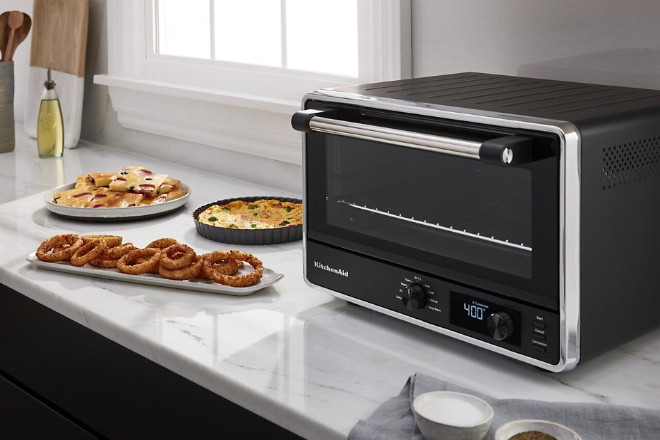 Air-fried onion rings on countertop next to KitchenAid® Countertop Oven with Air Fry.