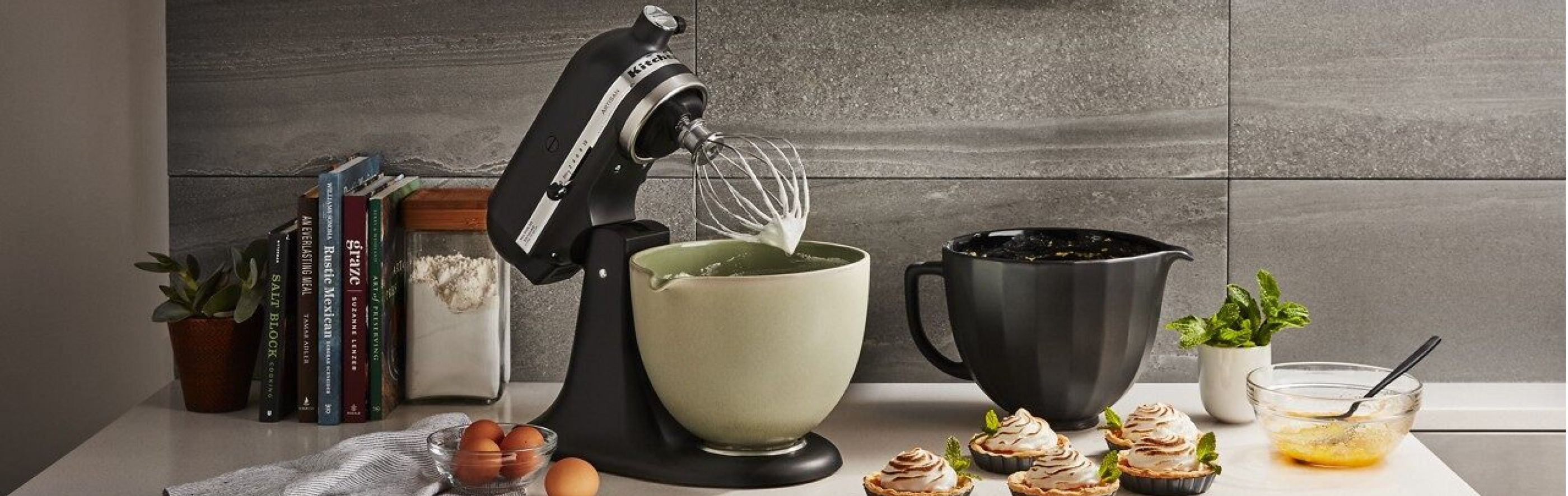 KitchenAid brand stand mixer on counter with four interchangeable ceramic mixer bowls
