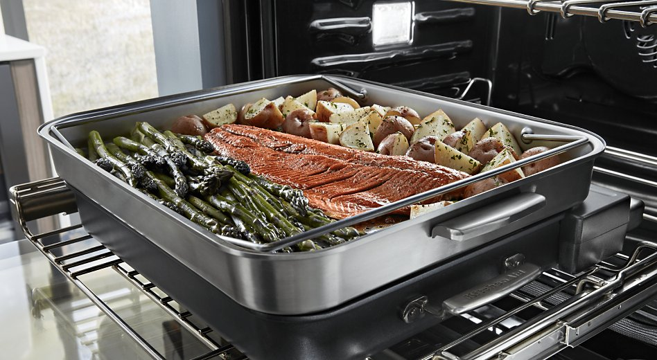 Salmon, asparagus and potatoes roasting in oven